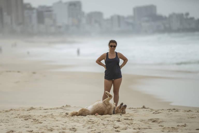 Mulher com cachorro na praia no Leblon, no Rio de Janeiro