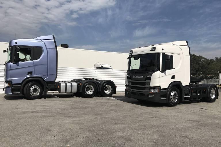 Dois caminhões, um azul e um branco, em pátio de fábrica