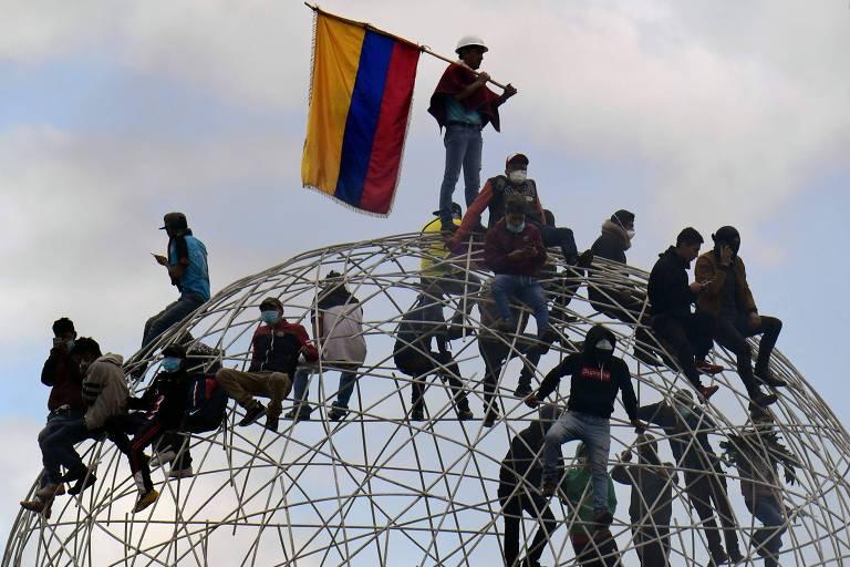 homens mascarados sobem em bola de metal com bandeira do equador