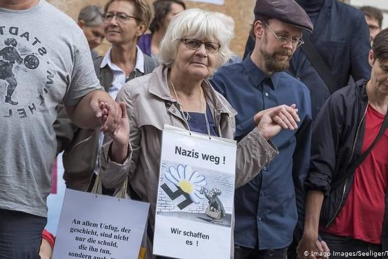 """Carregando a frase """"Fora, nazistas"""", Irmela Mensah-Schramm participa de manifestação contra o racismo em Berlim"""