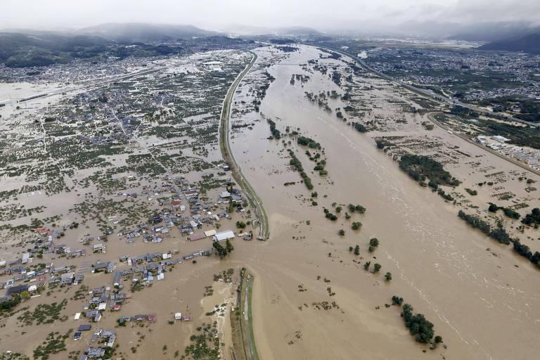Vista aérea de rio transbordado e cidade sendo inundada. A água tem cor de lama.
