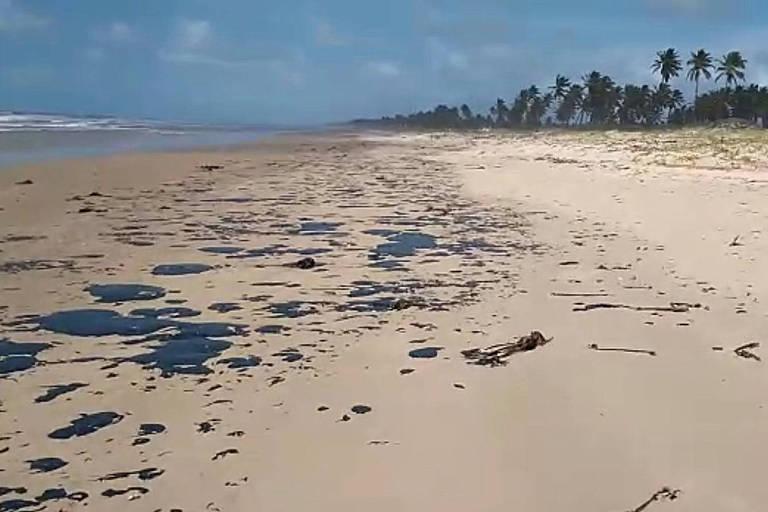 A areia da praia tem diversas manchas pretas de petróleo por toda a extensão