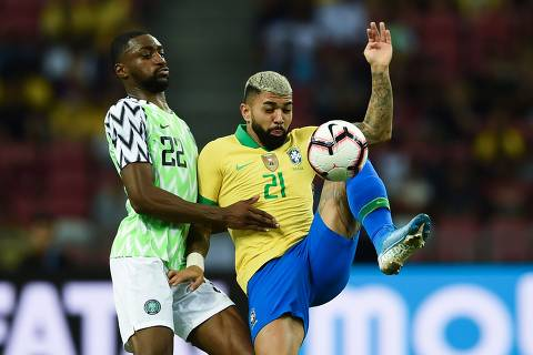 """CORRECTION - Brazil's forward Gabriel Barbosa (R) and Nigeria's defender Adesewo Ajayi fight for the ball during an international friendly football match between Brazil and Nigeria at the National Stadium in Singapore on October 13, 2019. (Photo by Roslan RAHMAN / AFP) / """"The erroneous mention[s] appearing in the metadata of this photo by Roslan RAHMAN has been modified in AFP systems in the following manner: [October 13] instead of [October 12]. Please immediately remove the erroneous mention[s] from all your online services and delete it (them) from your servers. If you have been authorized by AFP to distribute it (them) to third parties, please ensure that the same actions are carried out by them. Failure to promptly comply with these instructions will entail liability on your part for any continued or post notification usage. Therefore we thank you very much for all your attention and prompt action. We are sorry for the inconvenience this notification may cause and remain at your disposal for any further information you may require."""""""