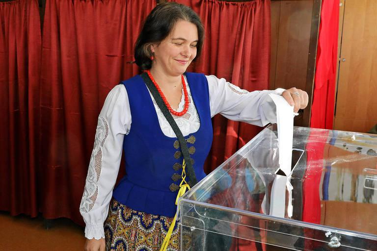 Com uma saia estampada e colete azul, em trajes característicos, a mulher deposita a cédula em uma urna.