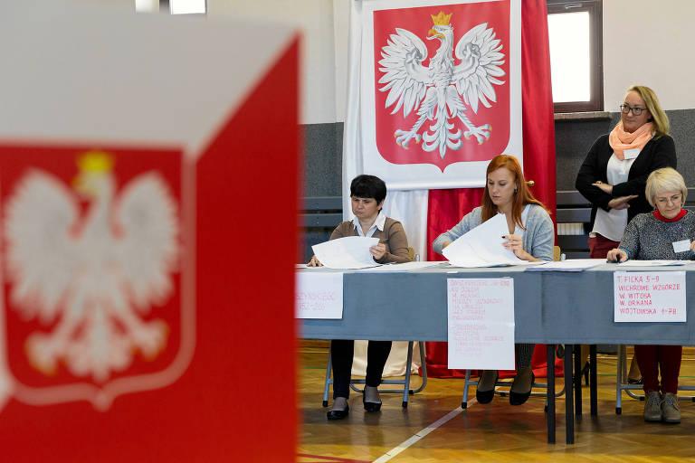 As mesárias estão sentadas em mesas cumpridas cobertas por toalhas azuis. O brasão vermelho e branco da polônia está estendido ao fundo.