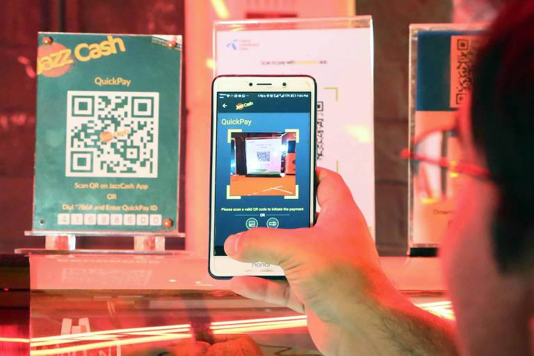 Homem paquistanês faz leitura de um QR Code para realizar pagamento