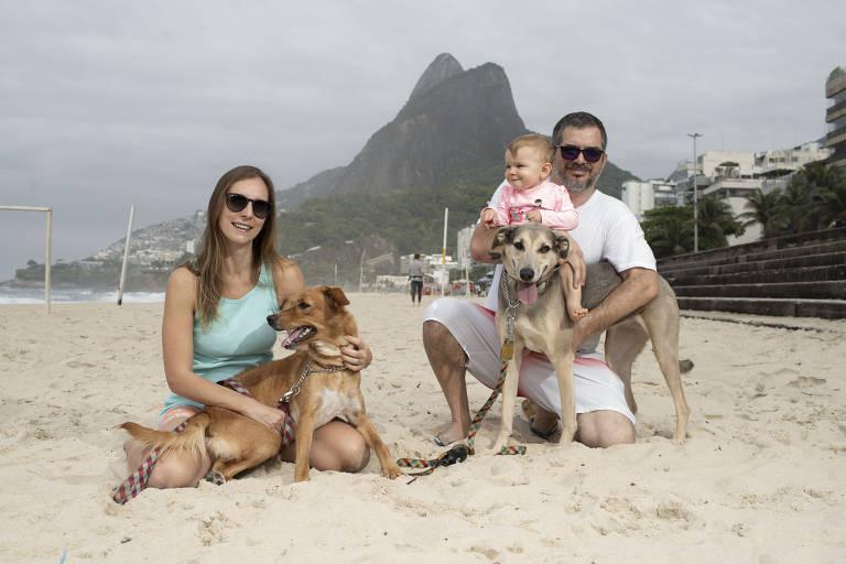 Alexandre Varella, Chloë Varella (bebê), Christiane Varella (mãe), com seus cachorros vira-latas, na praia do Leblon, no Rio