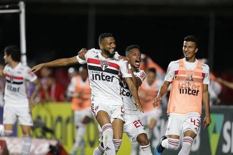 O lateral esquerdo são-paulino Reinaldo segurado pelo volante Tchê Tchê  comemora seu gol.