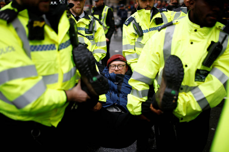 Policiais com coletes amarelos carregam homem deitado