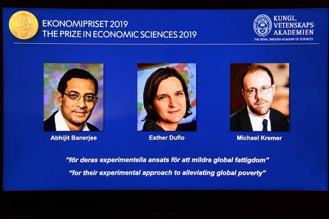 A computer screen displays the co-winners of the 2019 Sveriges Riksbank Prize in Economic Sciences in Memory of Alfred Nobel (L-R) Abhijit Banerjee, Esther Duflo and Michael Kremer during a press conference at the Royal Swedish Academy of Sciences in Stockholm, Sweden, on October 14, 2019. - Indian-born Abhijit Banerjee of the US, French-American Esther Duflo and Michael Kremer of the US won the Nobel Economics Prize for their