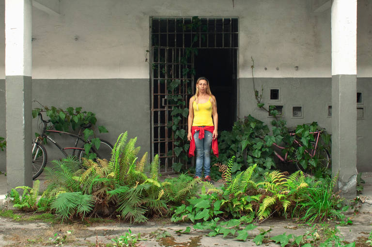 Mulher branca, loira e magra em frente a uma porta olha para espectador da foto
