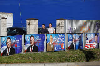 Men walk past the election posters, a day after parliamentary election, in Raszyn