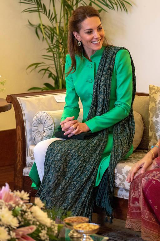 Sentada e de roupa verde, Kate Middleton sorri