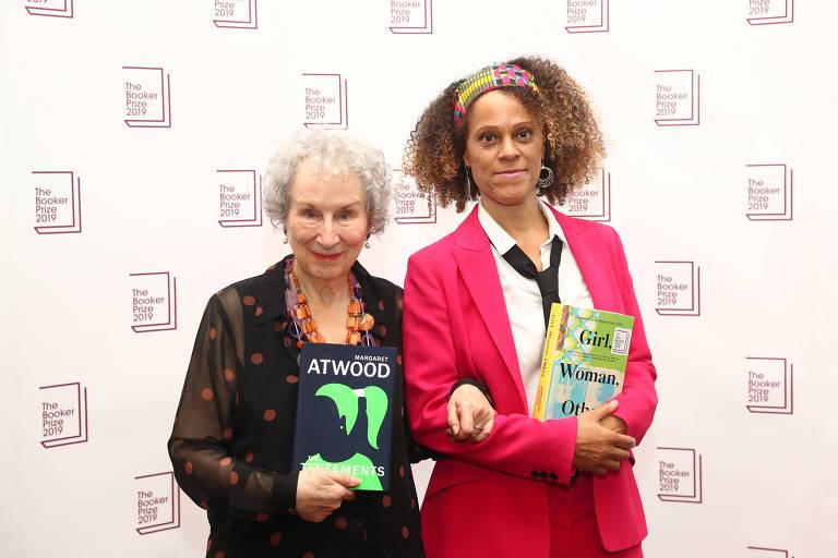 duas mulheres segurando um livro cada