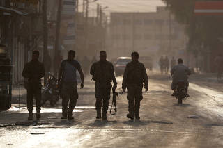 Turkey-backed Syrian rebel fighters walk together in the border town of Tal Abyad