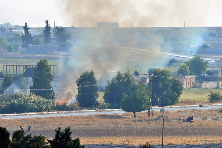 Imagem da cidade à distância, com fumaça subindo entre as árvores e casas