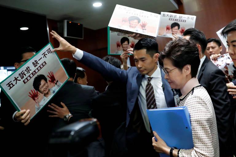 Líder de Hong Kong caminha cercada por opositores, que seguram cartazes