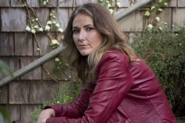 Mulher, com jaqueta vermelha, sentada