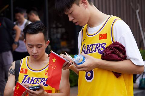 Fans wear Los Angeles Lakers shirts with Chinese flags before attending an National Basketball Association (NBA) pre-season game between the Los Angeles Lakers and the Brooklyn Nets in Shenzhen, in China's southern Guangdong province on October 12, 2019. (Photo by STR / AFP) / China OUT