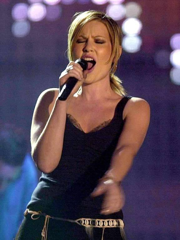 Mulher cantando com microfone na mão