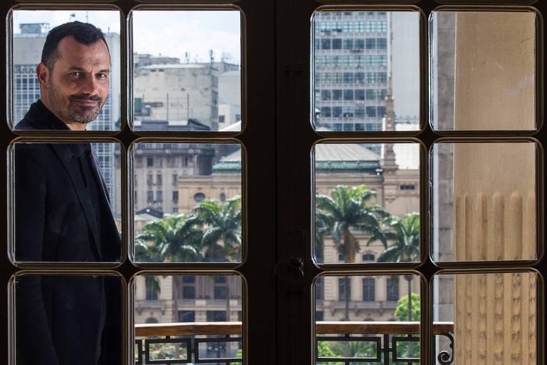 Alê Youssef, que deixa a secretaria municipal de Cultura no próximo dia 20; é um homem moreno, com barba bem curta, vestindo terno preto, que aparece fotografado através de uma vidraça do prédio da secretaria,  no centro da cidade; ao fundo avista-se o Theatro Municipal