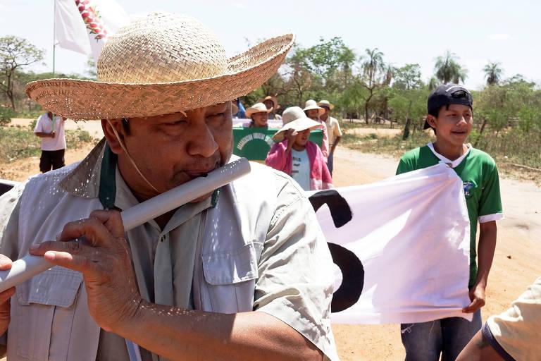 Com chapéu, indígena toca flauta durante caminhada
