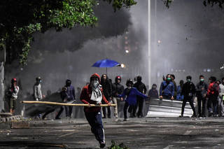 A protester carries a bamboo stick during clashes with police at a riot in Jakarta