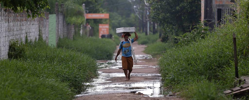 Homem caminha no conjunto habitacional Tauari, em Ananindeua, que sofre constantes alagamentos após chover, quando canais de esgoto invadem as casas