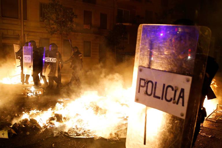 Policiais usam escudo ao lado de fogo aceso na rua