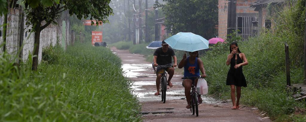 Moradores caminham no conjunto habitacional Tauari, em Ananindeua, que sofre constantes alagamentos após chover, quando canais de esgoto invadem as casas