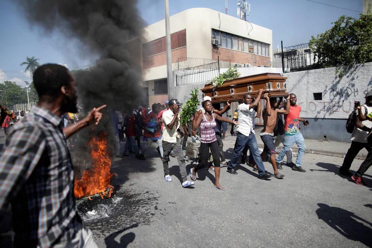 Caixão é carregado por várias pessoas ao lado de manifestantes e de fogo