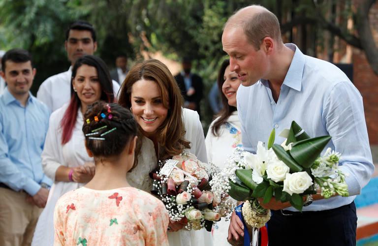 Príncipe William e Kate seguram flores enquanto conversam com criança, que está de costas. Eles sorriem