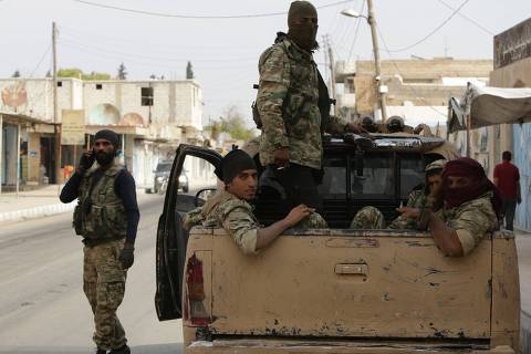 Turkish-backed Syrian fighters sit in the back of a truck in the Syrian border town of Tal Abyad on October 17, 2019, as Turkey and its allies continue their assault on Kurdish-held border towns in northeastern Syria. - US Vice President Mike Pence met Turkish President Recep Tayyip Erdogan on Thursday to push for a ceasefire in Syria after Ankara rebuffed international pressure to halt its deadly offensive against Kurdish forces. (Photo by Bakr ALKASEM / AFP)