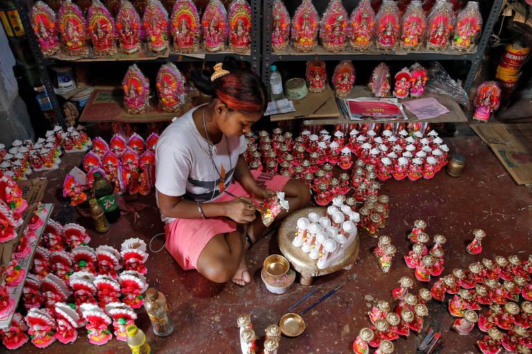 Mulher sentada no chão pinta representações de deuses, que estão em sua volta