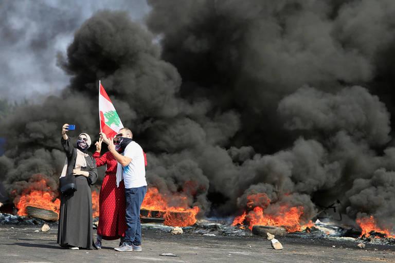 Manifestantes fazem selfie em frente a barricada durante protesto em Beirute contra governo do Líbano