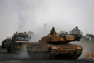 Turkish army vehicles are moving on a road near the Turkish border town of Ceylanpinar