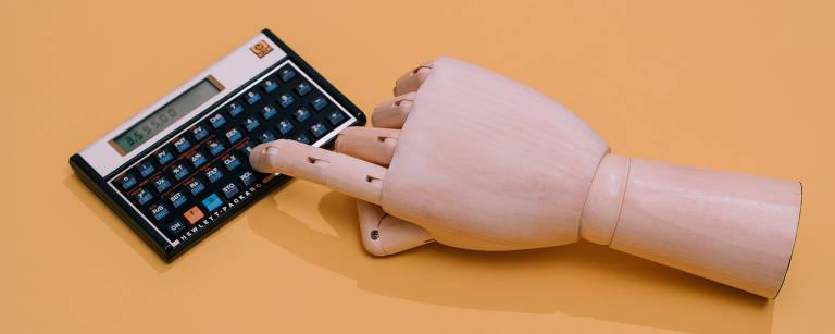 Um mão de madeira digita em uma calculadora científica
