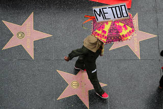 FILE PHOTO: A demonstrator takes part in a #MeToo protest march for survivors of sexual assault and their supporters in Hollywood, Los Angeles