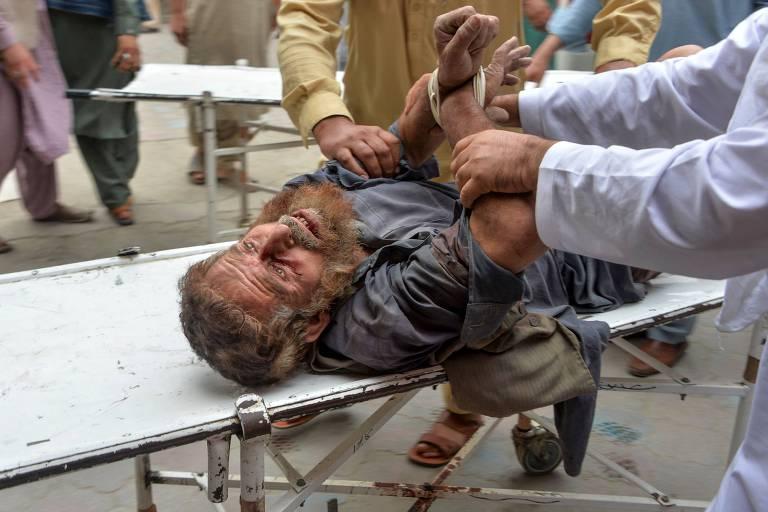 Voluntários carregam homem ferido após ataque a mesquista na província de Nangarhar