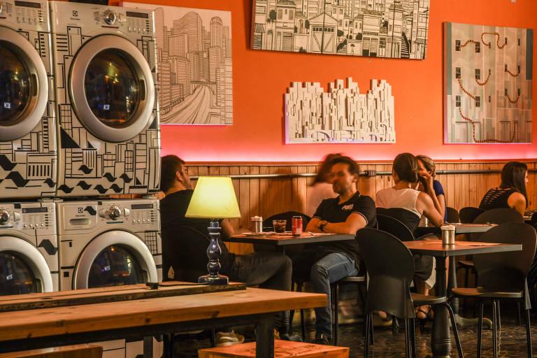 Clientes almoçam ao lado das máquinas de lavar na Laundry Deluxe, que fica nos Jardins, em São Paulo, que mistura lavanderia, restaurante e sushi-bar