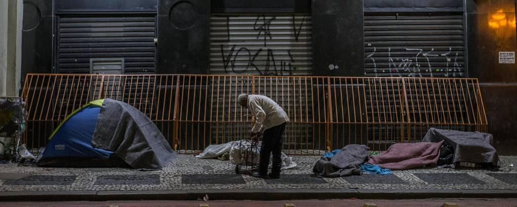 Morador de rua arruma carrinho durante noite fria de junho no centro de São Paulo enquanto outros dormem, cobertos