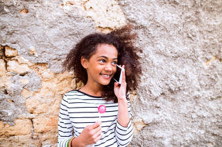 Pretty african american girl with smart phone, eating lollipop