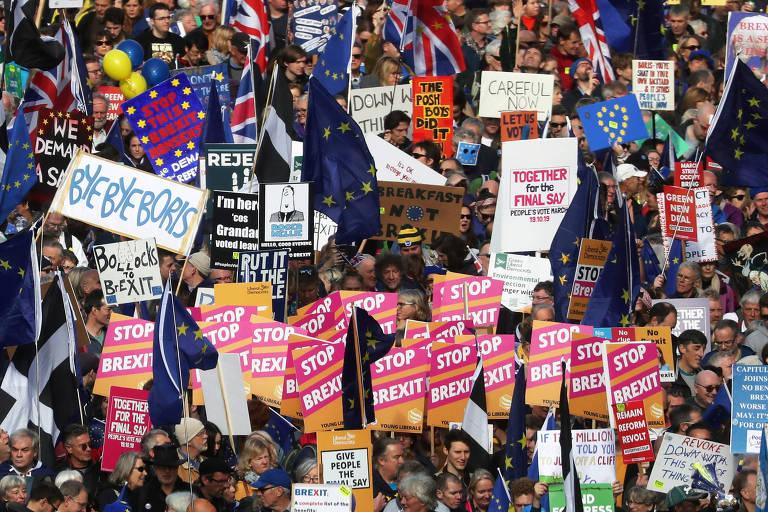 """Muitos manifestantes se reúnem segurando cartazes vermelhos com letras brancas em que se lê """"Pare o brexit""""."""