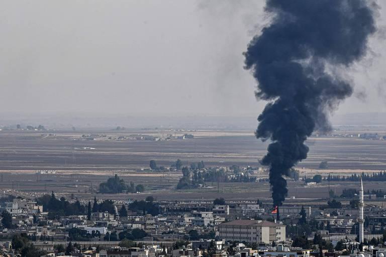Fogo e fumaça na cidade síria de Ras al-Ain, que foi invadida por forças da Turquia e milícia árabes apoiadas por Ancara