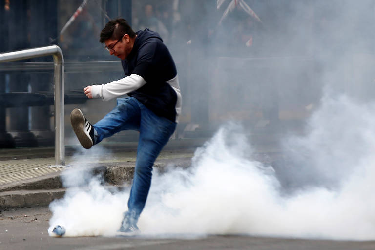 Manifestante chuta bomba de gás lacrimogêneo durante protesto contra aumento de tarifas do metrô, em Santiago