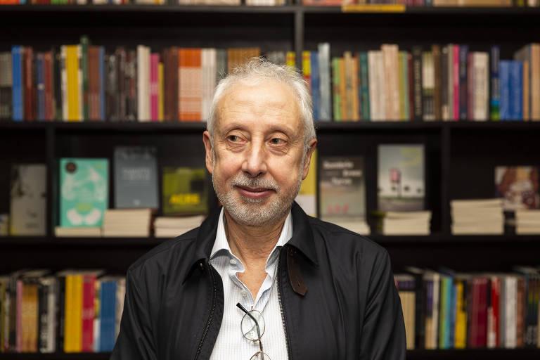O economista Pérsio Arida em frente a uma estante cheia de livro