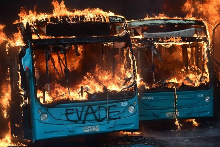 Ônibus queimados em protesto na plaza de Maipu, em Santiago, no sábado (19)