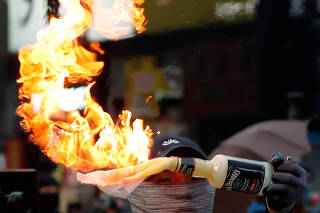 An anti-government protester holds a Molotov cocktail during a march in Hong Kong