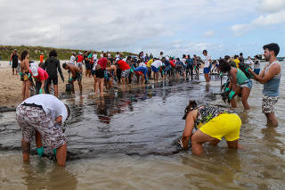 People work to remove an oil spill on Suape beach in Cabo de Santo Agostinho