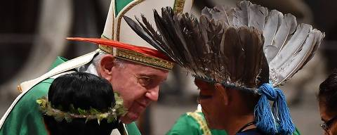 Representatives of one of the Amazon Rainforest's ethnic groups (Front) takes part in Pope Francis' (L) mass on October 6, 2019 at St. Peter's Basilica in the Vatican, for the opening of the Special Assembly of the Synod of Bishops for the Pan-Amazon Region. - Pope Francis will gather Catholic bishops at the Vatican on October 6 to champion the isolated and poverty-struck indigenous communities of the Amazon, whose way of life is under threat. (Photo by Tiziana FABI / AFP)